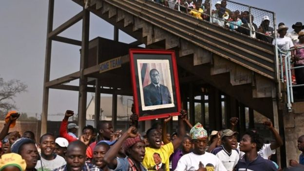 People carry a portrait of Robert Mugabe at Harare's stadium. Photo: 12 September 2019