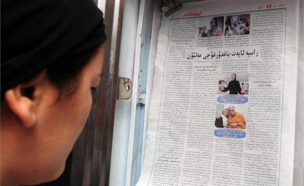 新疆的維族女性在看刊有熱比婭和達賴喇嘛照片的維文報紙。