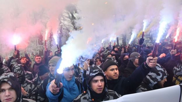 Activists of Ukrainian far-right parties hold flares during a rally at the Ukrainian parliament