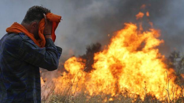 Bomberos y voluntarios intentan extinguir el fuego que se prendió en terrenos boscosos en Penteli, Grecia, el 23 de julio de 2018.