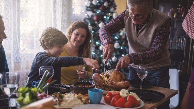 Família come ceia de Natal ao redor de uma mesa, com árvore decorada ao fundo