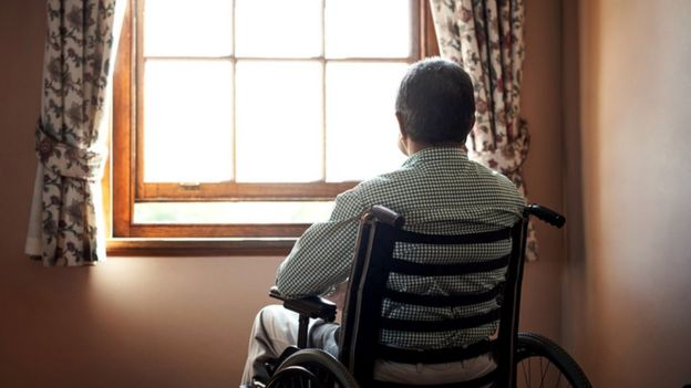 Man in a wheelchair looking out of a window