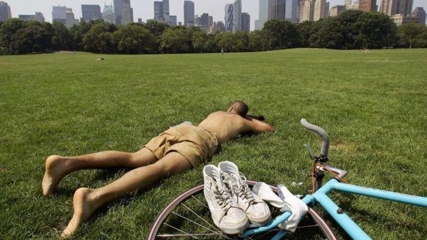Homem pega sol sobre a grama; há estudos que mostram que estender foco e produtividade é autodestrutivo