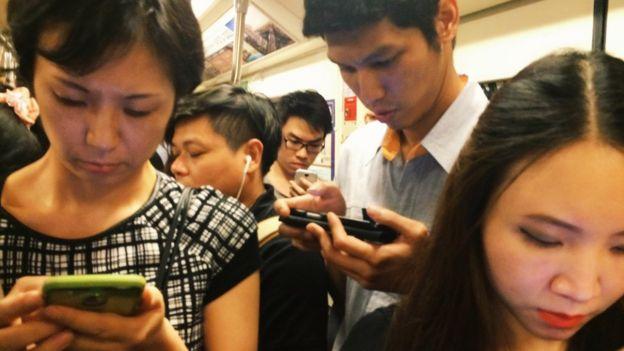 gente en el metro usando celular