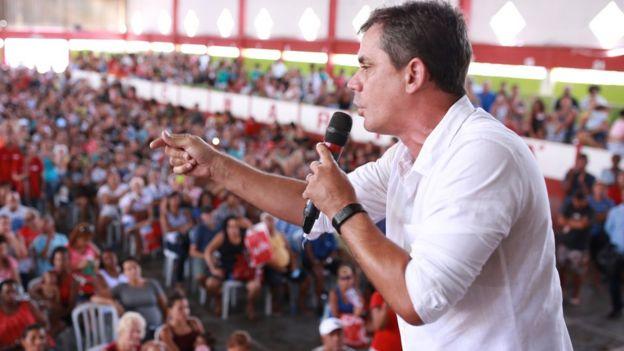 O prefeito Fabiano Horta em cerimônia de entrega do cartão, falando no microfone e observado pela população na plateia