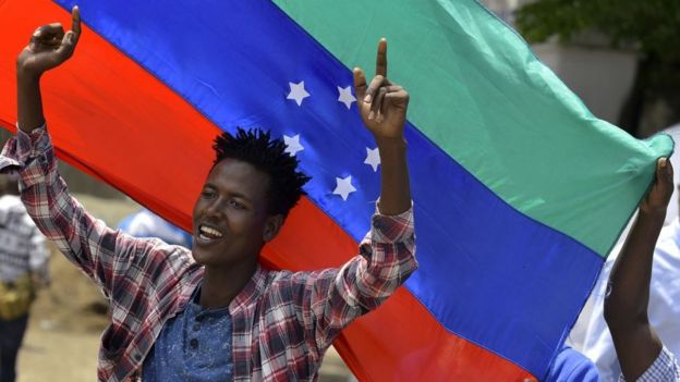 A protester waves the unofficial turqouisem blue and red Sidama flag