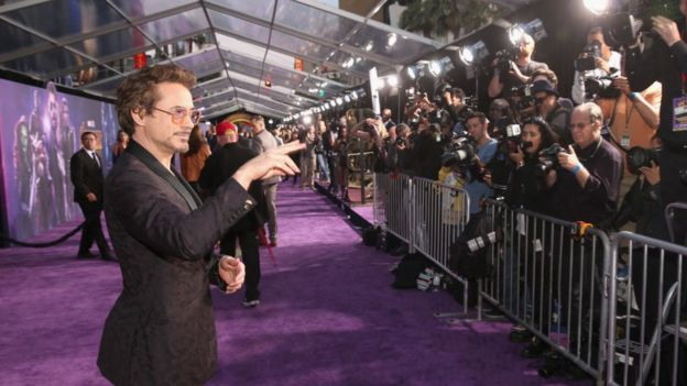 Robert Downey Jr stands in front of photographers on the red carpet at the Avengers: Infinity War premiere in Los Angeles