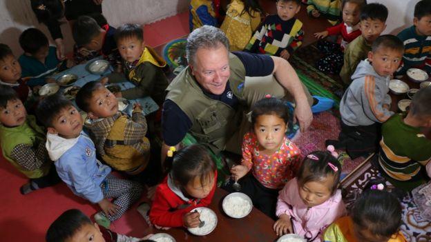 David Beasley rodeado de niños
