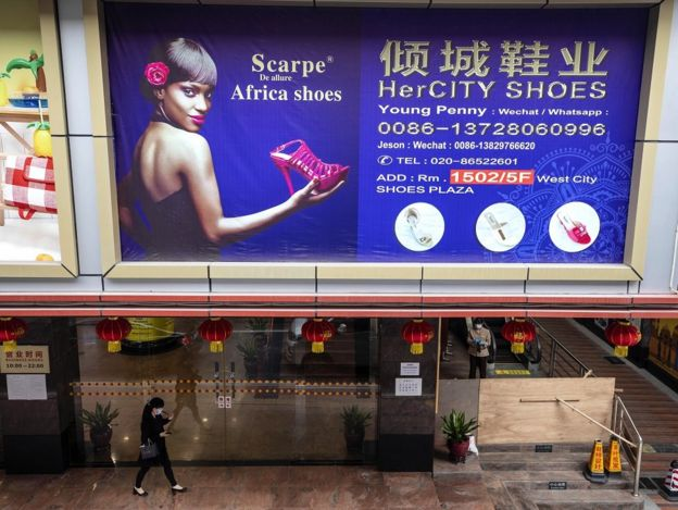 A woman passes by billboard in part of the town where most of the African people lives and works in Guangzhou, Guangdong province, China, 13 April 2020.