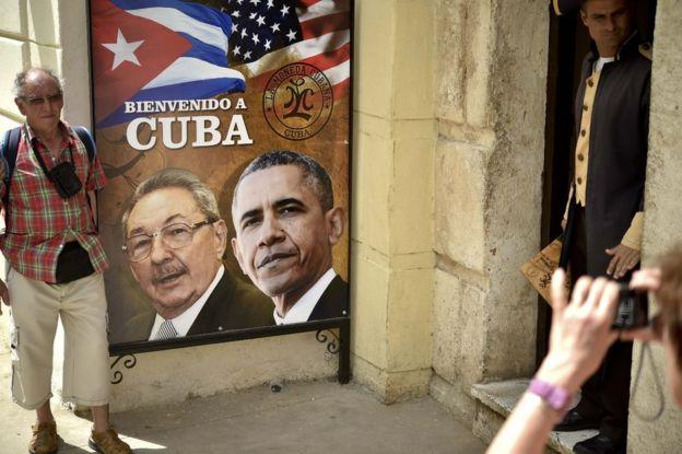 Bir turist, Küba ve ABD Başkanları Raul Castro ve Barack Obama'nın Havana, Küba'daki görüntüleri ile bir restoranın girişinde yer alan bir işaret poz veriyor