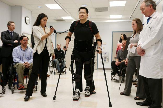 un hombre camina con un exoesqueleto.