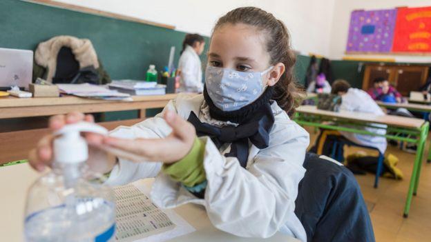 Escolar uruguaya con mascarilla y usando alcohol en gel.