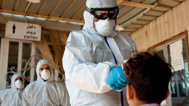 ماموران بهداشتی عراق در حال کنترل مسافران ورودی از ایران در مرز شلمچه