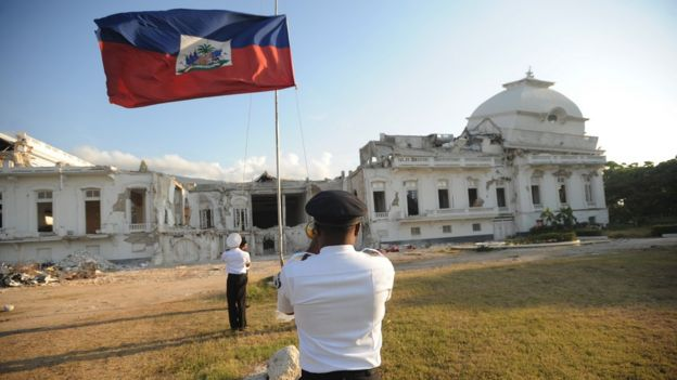 Haitian presidential guards lower the Haitian flag on April 19, 2011 in front of the destroyed presidential palace in Port-au-Prince