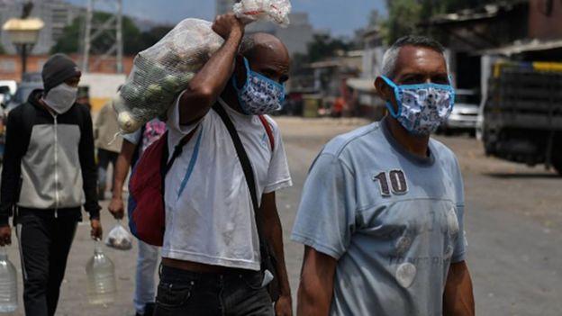 Hombres en Venezuela con mascarillas y alimentos.