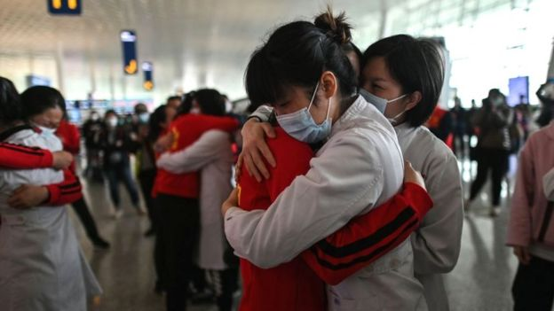 Medical staff from Jilin Province (in red) hug nurses from Wuhan after the Covid-19 lockdown was lifted, 8 April 2020
