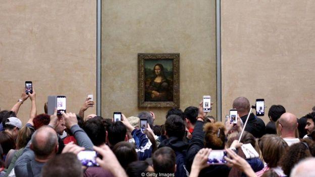 Pessoas fotografam o quadro da Monalisa