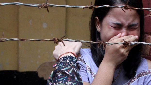 Chit Suu Win, wife of Reuters journalist Kyaw Soe Oo, is seen crying behind barbed wire after the verdict