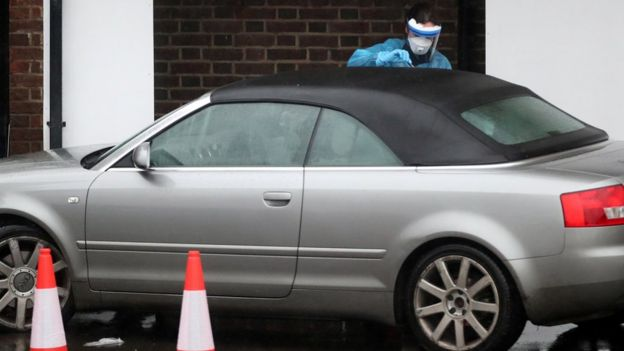 A medical worker carries out a test at a coronavirus drive-through test centre at Parson's Green Medical Centre in London