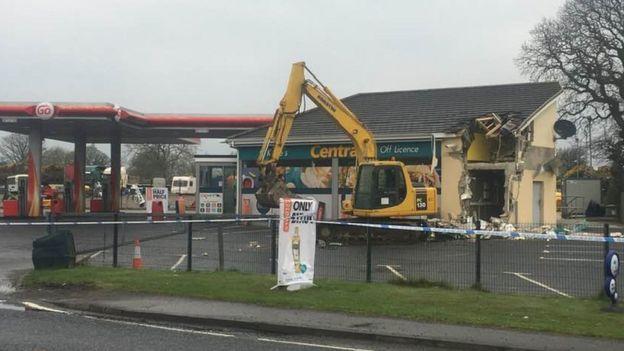 imagem do posto de gasolina com a escavadeira deixada para trás