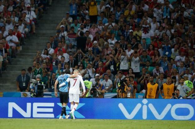 Cavani, lesionado, es ayudado por Ronaldo a salir del campo.
