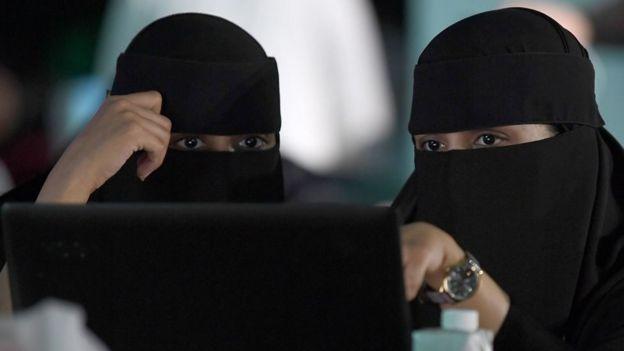 Bir laptop ekranına bakan peçeli Suudi kadınlar.