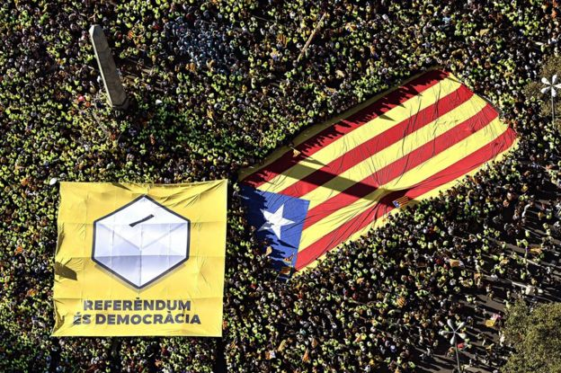 Thousands of people carry a giant Catalan separatist flag and a banner reading Referendum is Democracy in Barcelona, 11 September