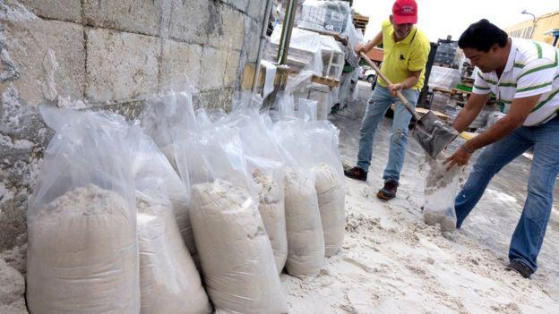 Un señor llena el saco de otro señor con arena, utilizada para frenar el paso del agua