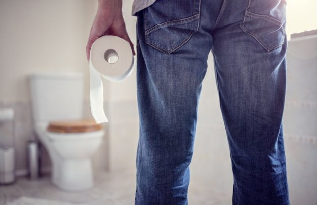 A man holds a roll of toilet paper.