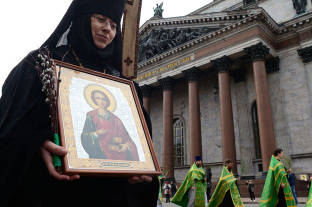 Russian Orthodox nun carries an icon outside St Isaac's Cathedral in St Petersburg, 9 Apr 17
