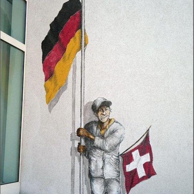 Mural de um homem segurando uma bandeira alemã e uma suíça em Büsingen