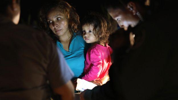 Madre Salvadoreña con su hija de dos años en brazos mientras la guardia fronteriza de EE.UU. inspecciona sus documentos