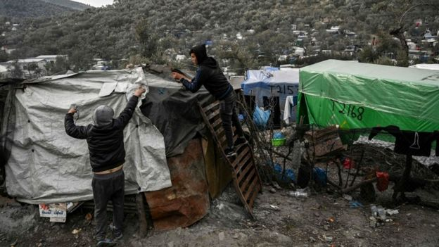 Two young men cover their shelter with plastic sheets at a makeshift camp in Moria, in the island of Lesbos, 21 January 2020