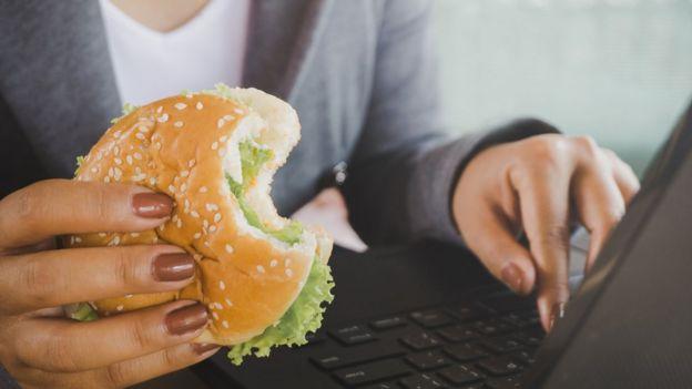 Una mujer frente a una computadora con una hamburguesa.