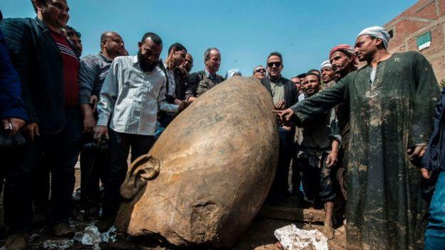 El ministro de antigüedades egipcio y otros hombres posan junto a una porción de la estatua.