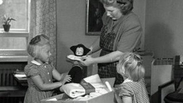 Una madre muestra a dos niñas el contenido de la caja en 1947 (Foto: Museo del Trabajo de Finlandia Werstas)
