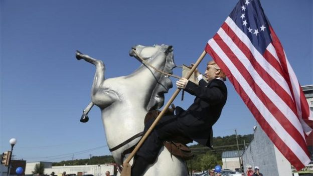 Estatua de Donald Trump sobre un caballo y llevando la bandera Betsy Ross.