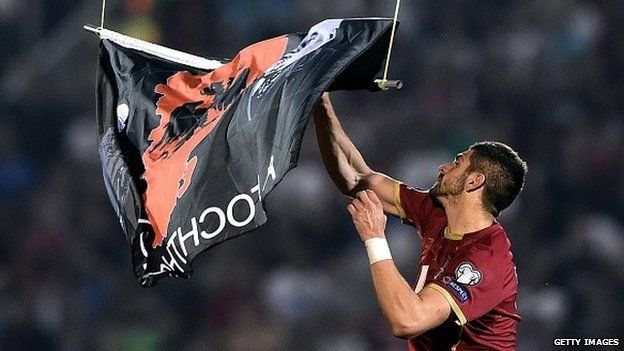 Serbia's Stefan Mitrovic grabs a flag with Albanian national