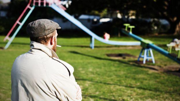 Un hombre de espaldas observando niños en un parque.