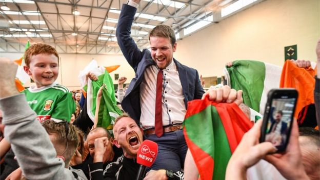 Sinn Fein's Donnchadh Ó Laoghaire celebrates being the first TD elected to the 33rd Dáil, topping the poll ahead of Micheál Martin in cork