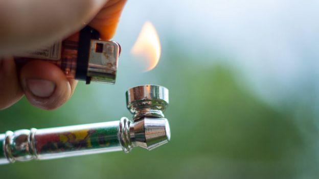Encendiendo una pipa de marihuana.