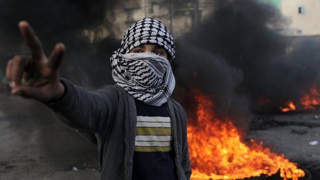 فلسطيني يرفع علامة النصر امام إطار محترق في غزة