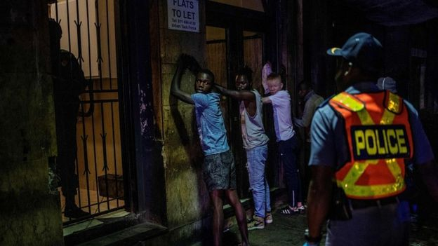 Suspects are lined up against a wall as a police officer wearing gloves arrests them because they defied the lockdown order during an operation in Johannesburg, on March 27, 2020