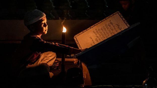 মোমবাতির আলোয় কুরান পড়ছে ইন্দোনেশিয়ার শিশু