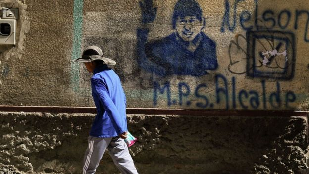 Una persona camina frente a una pared con una imagen de Evo Morales
