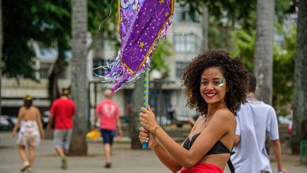 Mulher com glitter no rosto segura porta-estandarte no Carnaval