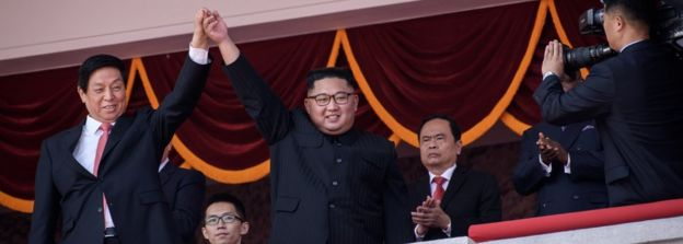 North Korea's leader Kim Jong Un (centre R) waves with China's Chairman of the Standing Committee of the National People's Congress Li Zhanshu
