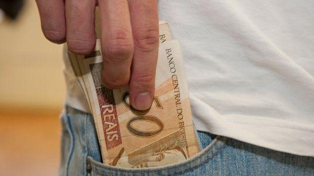 Homem coloca cédulas no bolso