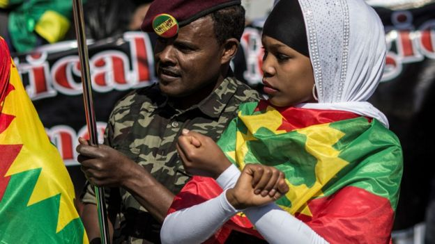 A demonstrator (L) dressed in military fatigue joins members of the Oromo, Ogaden and Amhara community in South Africa as they demonstrate against the ongoing crackdown in the restive Oromo and Amhara region of Ethiopia on August 18, 2016 in Johannesburg