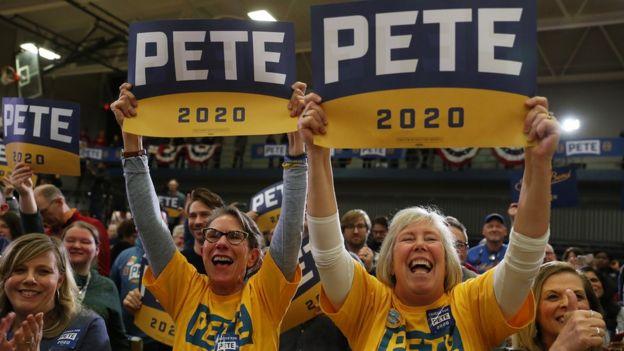 женщины держат плакаты в поддержку кандидата Пита